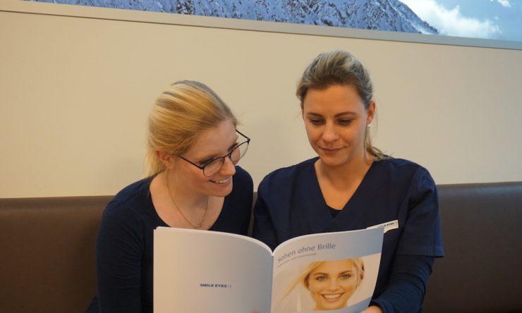 Carina zeigt Patientin die Smile Eyes Broschüre